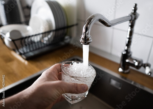 Fényképezés male's hand pouring water into the glass from chrome faucet to drink running water with air bubbles