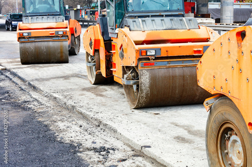 Photo Large and heavy orange vibratory rollers stand on the roadway awaiting work