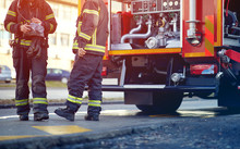 Profesional Fire Truck With Fire Fighting Equipment And Firemen In Protective Clothing, Helmets.