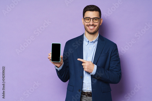 Papel de parede Young business man in suit, wearing eyeglasses, holding blank screen smartphone