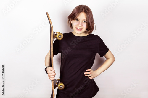 A teenage girl smiling happily and holding a skateboard, any sport makes her hap Fototapet