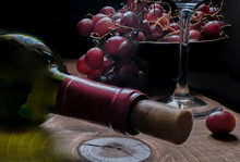 Still Life Macro Photography Of Bottle Of Wine And Red Grapes In A Bowl On The Background In Low Key Light Or Dark Food. On A Rustic Wooden Table.