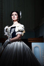 Beautiful Girl, In A Romantic Dress, Retro Style.With Dark Hair. He Stands In Full Height, Against The Background Of The Stage In The Theater, And Looks Away. Historical Reconstruction