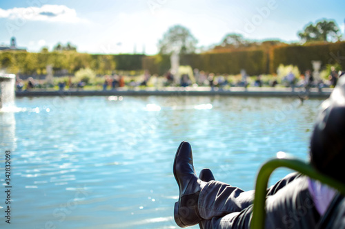 Photo A Parisian man relaxes with his feet resting on the Gran Bassin Rond fountain in