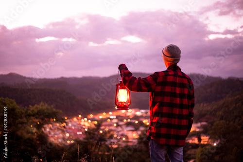 Young man contemplating the city lights with a kerosene lamp lit Slika na platnu
