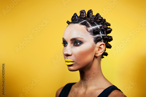Portert girl on a yellow background of Caucasian-Asian appearance with a creativ Canvas Print