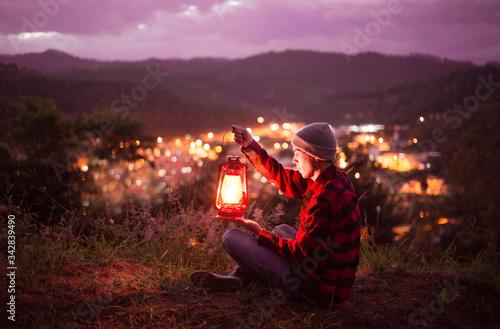 Fotografija Young man contemplating the city lights with a kerosene lamp lit
