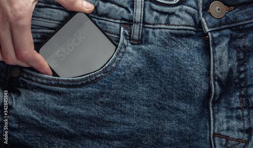 Hand pulls smartphone out of front jeans pocket Fototapeta