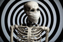 A Skeleton Wearing A Cloth Medical Face Mask In Front Of A Hypnotic Spiral Background. Conspiracy Or Confusion Over The Covid-19 Coronavirus Pandemic.