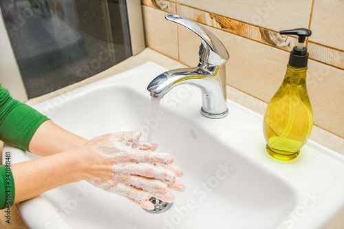 A Hands with soap are washed under the tap with water Wallpaper Mural