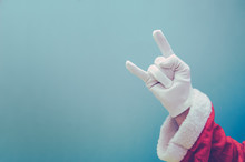 Cropped Hand With Santa Claus Costume Showing Rock Sign Against Blue Background