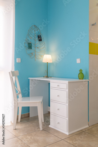 white desk and chair in a bright airy room with blue walls. Canvas Print
