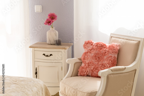 Bright and airy sitting corner with baige chair and pink pillow. Canvas Print