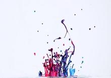 Closet-up Of Colorful Splashing Paints Against White Background