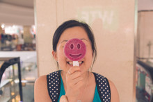 Happy Young Woman Holding Smiley Face Lollipop At Restaurant