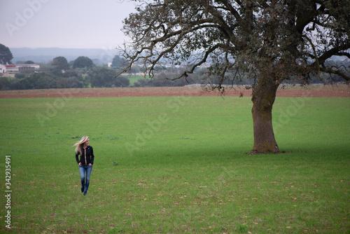 Obraz na plátně Donna passeggia in un prato attorno a un albero di quercia nella campagna in Puglia