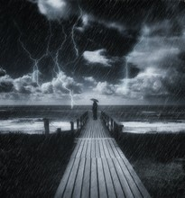 Silhouette Man Standing On Pier Against Sky During Thunderstorm