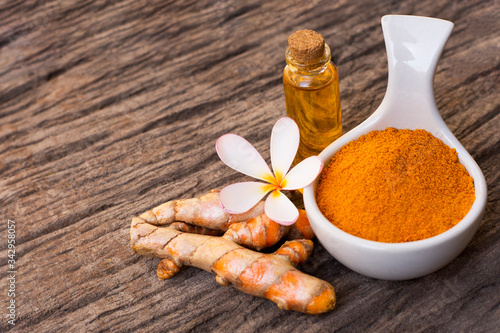 Photo Tumeric ( curcumin, curcuma longa Linn) powder in white ceramic bowl  with root and bottle of turmeric essential oil extract isolated on old wood table background
