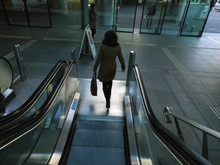 Silhouette Woman Walking Towards Escalator In Building