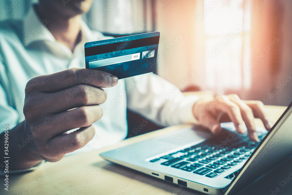 Fototapeta Young man use credit card for shopping payment online on laptop computer application or website. E-commerce and online shopping concept.