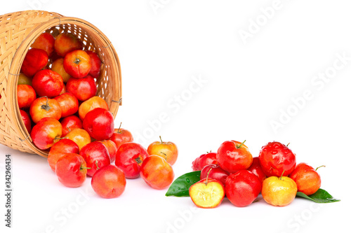 Closeup fresh small red organic  acerola cherry fruits (Malpighia Glabra) with green leaf in wooden bowl isolated on white background Wallpaper Mural