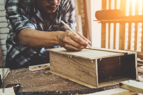 Photo Carpenter working on wood craft at workshop to produce construction material or wooden furniture