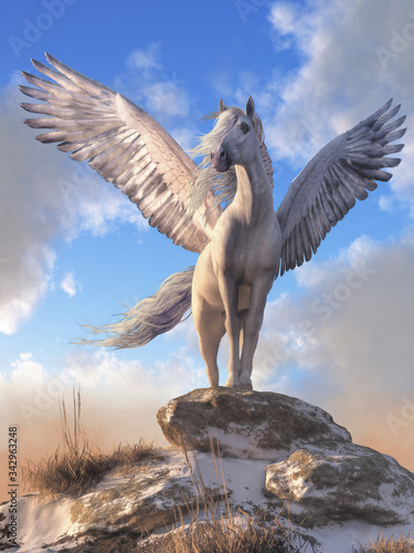 Fotografija Pegasus, the all white, horse with wings from Greek mythology stands atop a rock covered hill top, his white feathered wings spread wide
