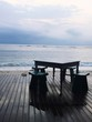 Empty Table And Chairs On Pier At Beach Against Sky