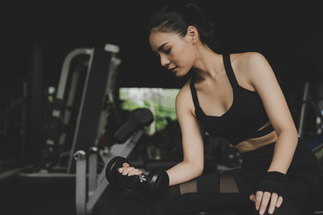 Fototapeta na wymiar strong pretty asian slim body woman in black sport bra exercise with dumbbell in fitness gym in background, bodybuilder, healthy lifestyle, exercise fitness, workout and sport training concept