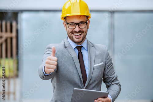Attractive caucasian smiling elegant architect in suit, with eyeglasses and helmet on head holding tablet while standing at construction site and giving thumbs up Poster Mural XXL