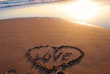 High Angle View Of Heart Shape With Text On Wet Shore During Sunset