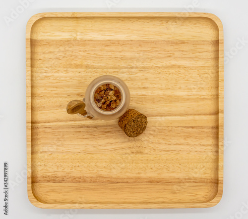 Photo Rock sugar in mini glass tank and cork lid on wooden cutting board and empty space for add on isolated on white