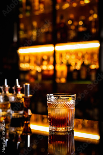 Photo A cocktail in an old fashioned glass on a bar counter with a reflection, bottles