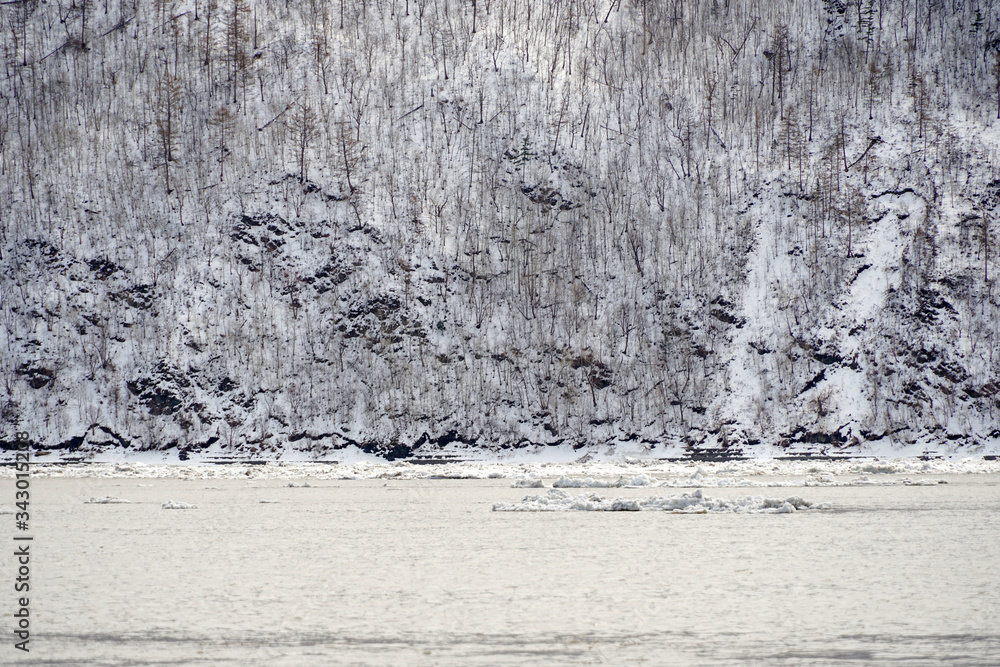 ice drift on a big river, ice floes floating on the water, against the backdrop of black and white motley hills, Russia, Amur, Far East