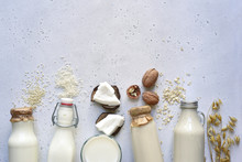 Alternative Types Of Vegan Milks In Glass Bottles. Top View With Copy Space.