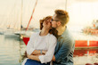 Loving cheerful couple of lovers sitting on a bench against the background of yachts club at sea. Romantic, love story concept