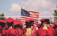 Rear View Of Graduates Standing Against American Flag During Sunny Day