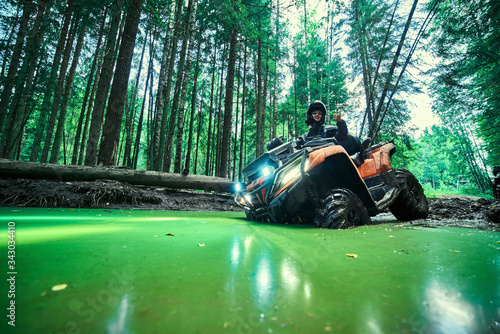 Fototapeta Beautiful girl on a ATV in a green swamp in the forest obraz
