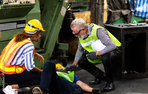 Obraz First Aid. Engineering supervisor talking on walkie talkie communication while his coworker lying unconscious at industrial factory. Professional engineering teamwork concept. - fototapety do salonu