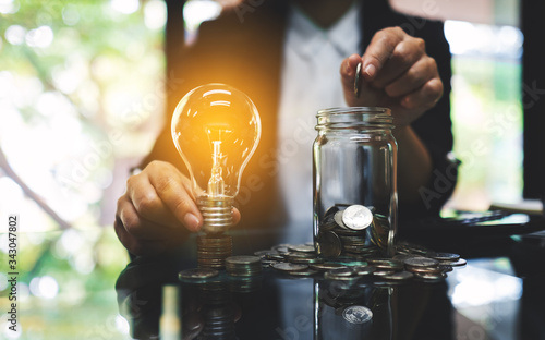Obraz Businesswoman holding a light bulb over coins stack on the table while putting coin into a glass jar for saving energy and money concept - fototapety do salonu