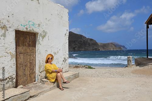 Photo mujer con sombrereo amarillo y vestido amarillo sentada casa playa mediterraneo