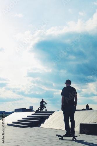 Rear View Of Man Skateboarding On Footpath