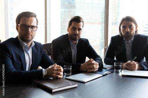 Fototapeta Portrait serious three businessmen employees sitting at table in modern boardroom, confident office workers wearing suits looking at camera, posing for corporate photo at briefing obraz na płótnie