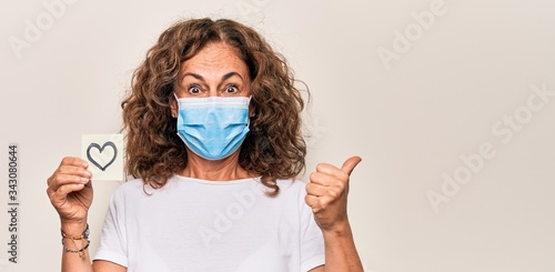 Cuadros en Lienzo Middle age woman wearing coronavirus protection mask and holding love reminder o