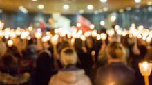 Defocused Image Of Crowd With Illuminated Candles In Church