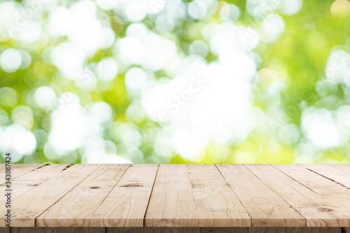 Obraz na plátně abstract blurred garden and green leaf with wooden table counter background for