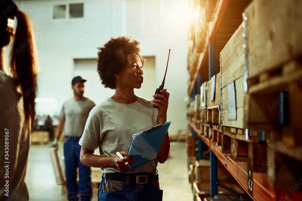 Fototapeta Black female dispatcher using walkie-talkie while working in distribution warehouse.
