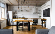An Eat-in Kitchen Interior Design In Modern Scandinavian Style With Big Wooden Table And Chairs Against Light Wood Floor, Bright White Walls And Furnitures With TV, Appliances And Hanging Light Bulbs