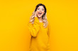 Teenager girl isolated on yellow background with surprise and shocked facial expression