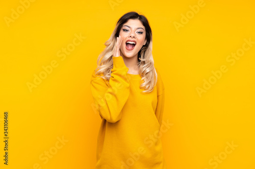 Teenager girl isolated on yellow background with surprise and shocked facial exp Fototapet